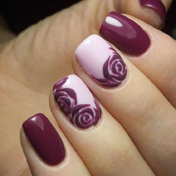 Beautiful magenta rose nail art design. The dark colors contrast greatly with the plain white background where the roses are painted also in magenta hue.