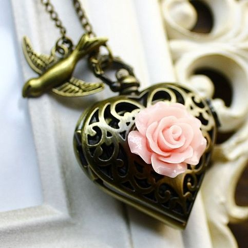 "Elegant, cute and delicate Victorian style heart shape bronze locket pocket watch necklace decorated with pink resin rose flower and small bird pendant. Chain included.  Shipping rates are calculated in base of weight.  Measurements:  Pendant size - 1.5""  Chain length - 31.5"""