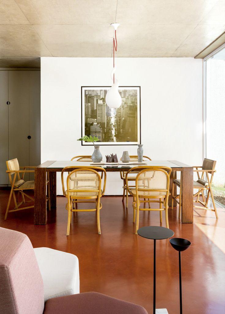A laje de concreto aparente dá um ar ainda mais despojado ao projeto. As peças sobre a mesa de jantar são da Dpot, e a foto na parede, de Cristiano Mascaro.