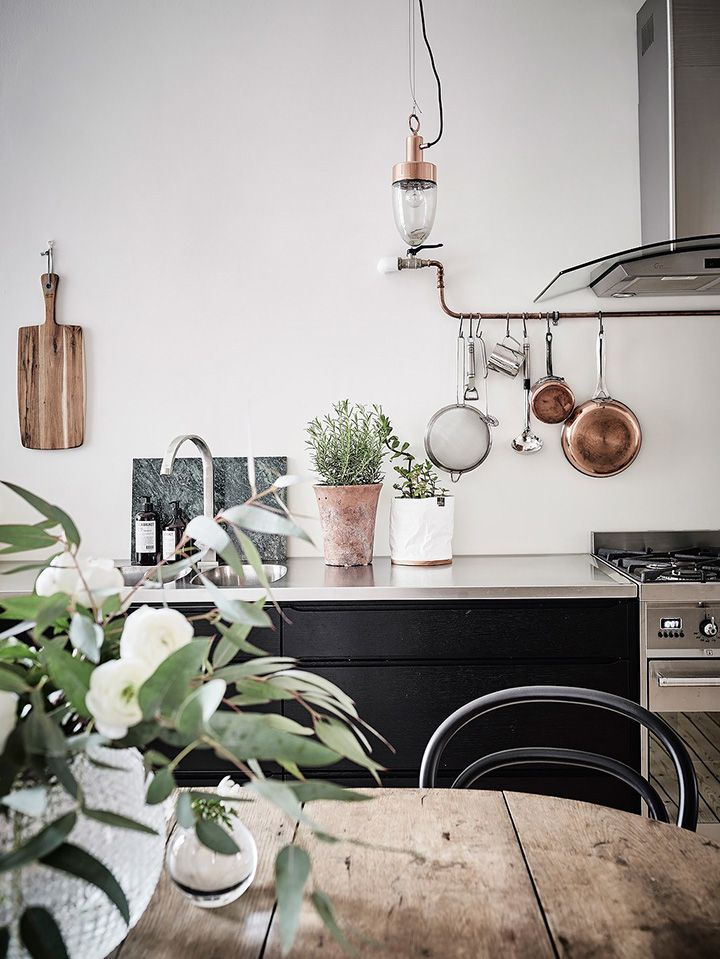 5 Scandinavian Design Ideals to Incorporate Into Your Kitchen | Wood table with potted plant, black cabinets, copper pots and fixture.