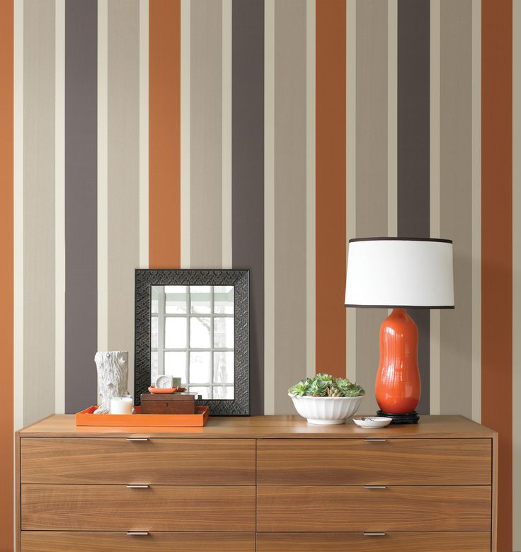 A striped wall feature wall with a mod orange and grey wallpaper