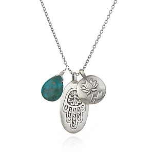 This triple charm necklace is a powerful amulet. Featuring a deep blue-green turquoise raindrop, a stunning oval pendant engraved with a Hamsa, and a raised lotus disc pendant, it is full of symbolism and meaning. Turquoise, the stone of healing, and the Hamsa which protects against negative energies, meet the lotus as a symbol of renewal and transformation.