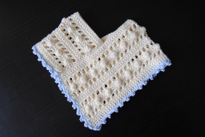 Miniature crochet poncho for a newborn baby.