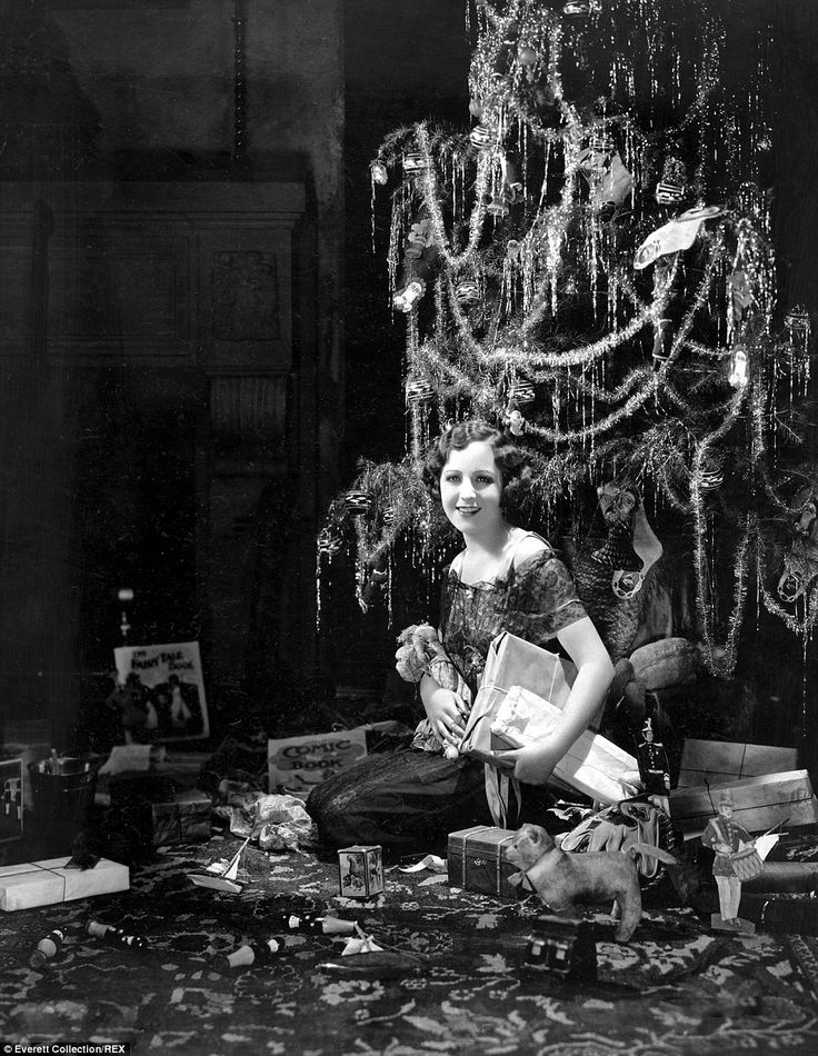 A woman sits at the foot of a tinsel-covered Christmas tree surrounded by  string