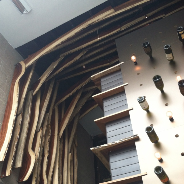 Two story restaurant entry way in Little Italy, San Diego. Lumber sections out to natural bark edge.
