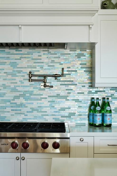 Beach style kitchen features a white kitchen hood over a satin nickel swing-arm pot filler lining a linear blue mosaic glass tile backsplash as well as a Wolf range.