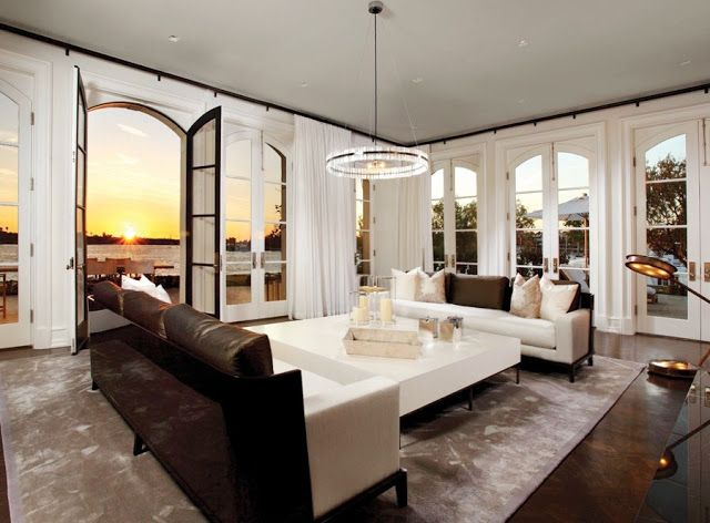 Dueling modern white and brown sofas face off in a the formal living room with its stunning water views and wrap around arched French doors. cococozy.com