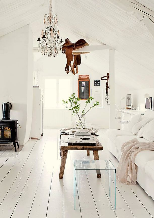 Pristine white farmhouse love the white wood floors and vthe saddle hanging across the beam
