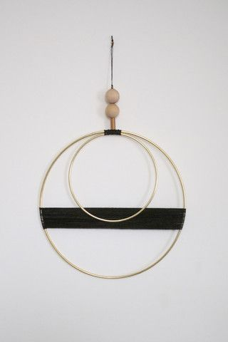 """Beautiful brass and waxed cord wall hanging with raw wood and vintage brass bead detail. Measurements: - Larger brass circle is 10"""" - Smaller brass circle is 6"""" - Beaded hanger above circles is 6"""" - T"""