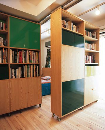Sliding bookcase/partitions.  Nozawa Apartment by architect Emanuelle Moureaux