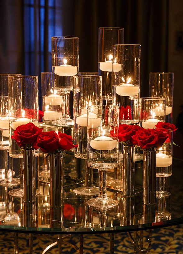 Such a stunning arrangement of red roses and lots of floating candles.