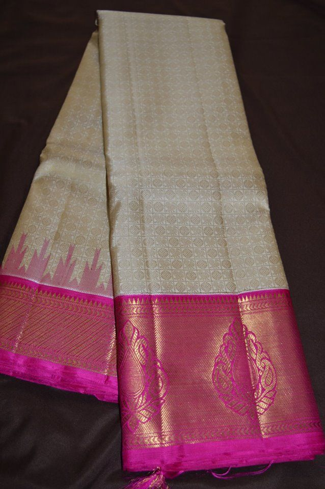 Pure silk pure zari kanchivaram saree in off white body with threadwoven peacock and chakram motifs nd zariwoven pink borde...