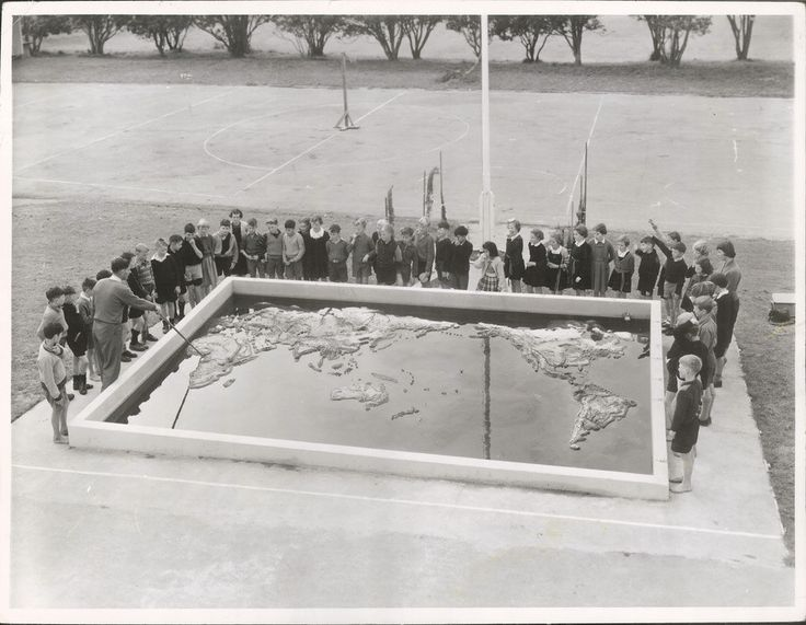 Mr. N. R. Jones takes a class in Geography at the concrete relief map of the world in the grounds of the May Road Primary School, Mt. Roskill, Auckland. | by Archives New Zealand