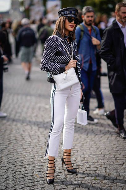 Camila Coelho wears a beret hat white pants a white bag a jacket outside Chanel during Paris Fashion Week Womenswear Spring/Summer 2018 on October 3...