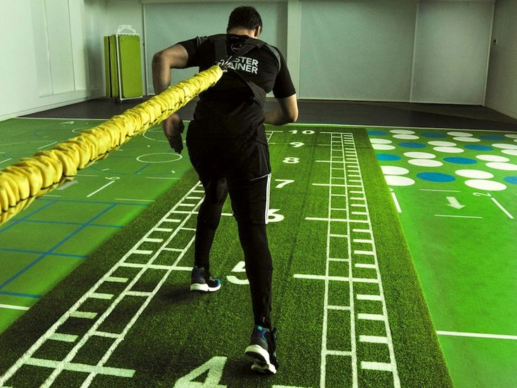 A personal trainer exercising on artificial turf using speed training exercises.