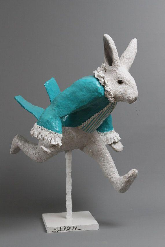 Sculpture en papier mâché du lapin dAlice au Pays des Merveilles avec sa redingote bleu turquoise, sa chemise blanche et son gilet à rayures bleues et blanches. Sa redingote vole au vent. La sculpture est fixée sur un socle en bois avec une tige métallique recouverte de tissu enduit. Elle est décorée avec de la peinture acrylique et recouverte dun vernis satiné. Elle est signée. cette sculpture est destinée à un usage intérieur.  Dimensions: Hauteur 75 cm x Longueur 55 cm x Largeur 44 cm…