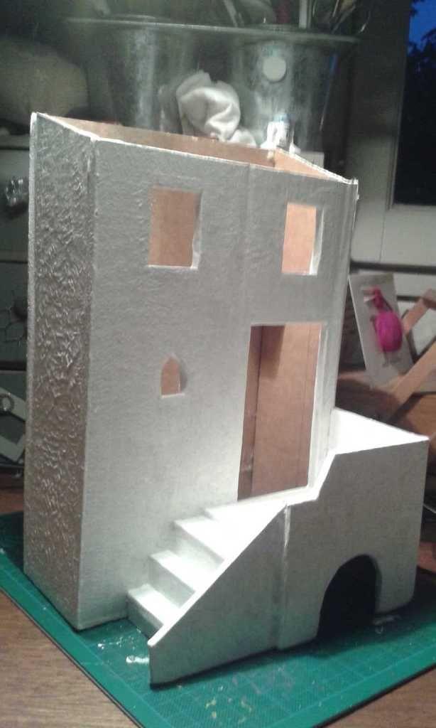Amélo utilise du Gesso pour peindre la façade et créer l'illusion du crépi en tapotant avec le pinceau (2couches suffisent à camoufler la rectitude du kraft dans les angles). Le Gesso se pose directement, sans avoir besoin d'eau.