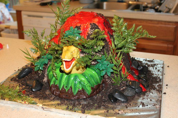 """Dinosaur Volcano Cake - I made this cake for my son's 4th birthday.  I used 6 cakes stacked on top of each other with the top being vanilla and the bottom chocolate then carved out my volcano form.  I used a cake """"topper"""" that has a motion sensor and the dino pops out of the cake if someone passes by!  I carved out a spot at the bottom for the dino too.  I then covered the cake in home made bettercream (not buttercream) then crushed oreo's.  I used fake plants for the foliage and and rocks…"""
