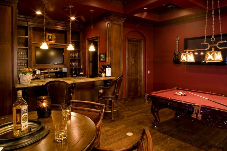 Classic man cave with a full bar and leather bar stools. Really love that the pool table matches the theme of the room.