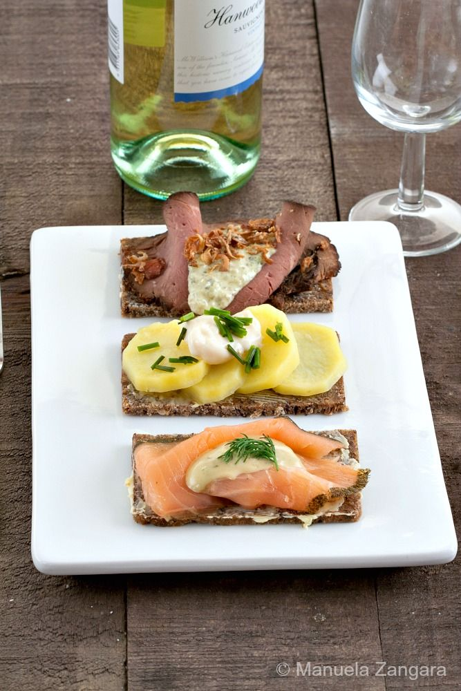 Smorrebrod - delicious Scandinavian open sandwiches made with buttered rye bread and topped with roast beef, gravlax or potatoes.