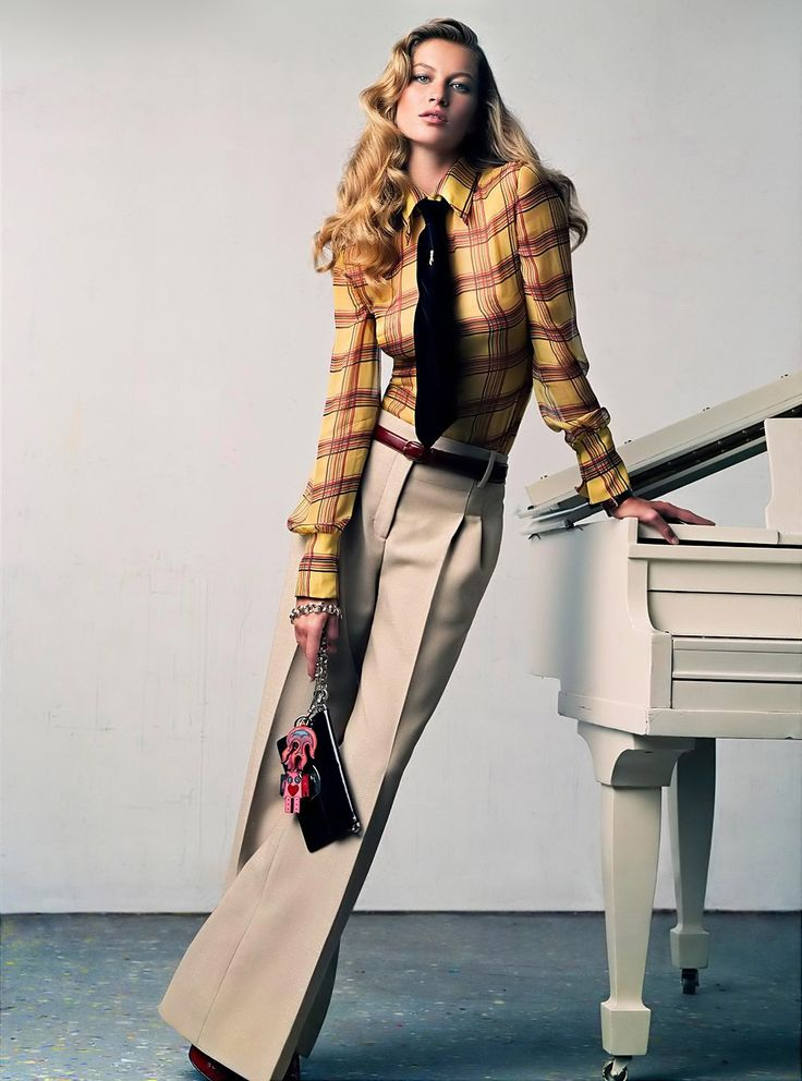 """Gisele Bündchen with white piano in """"About a Boy"""" for US Vogue, September 2004. Photograph by Craig McDean. """"Wilde child. As you gender-blend, mix stripes, plaids, and herringbone. Valentino mustard-and-paprika plaid blouse, about $1,980, Valentino boutiques. Marc Jacobs wide-leg oatmeal pants, about $785, Marc Jacobs stores. Valentino velvet necktie. Prada patent-leather purse. Robot charm, and fire charm."""""""