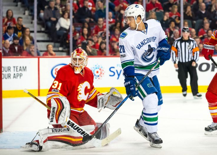 CALGARY, AB - JANUARY 07: Calgary Flames Goalie Chad Johnson (31) and Vancouver Canucks Center Brandon Sutter (20) follow the puck as it hits the back boards during a game between the Calgary Flames and the Vancouver Canucks on January 07, 2017, at the Scotiabank Saddledome, in Calgary AB. (Photo by Jose Quiroz/Icon Sportswire)