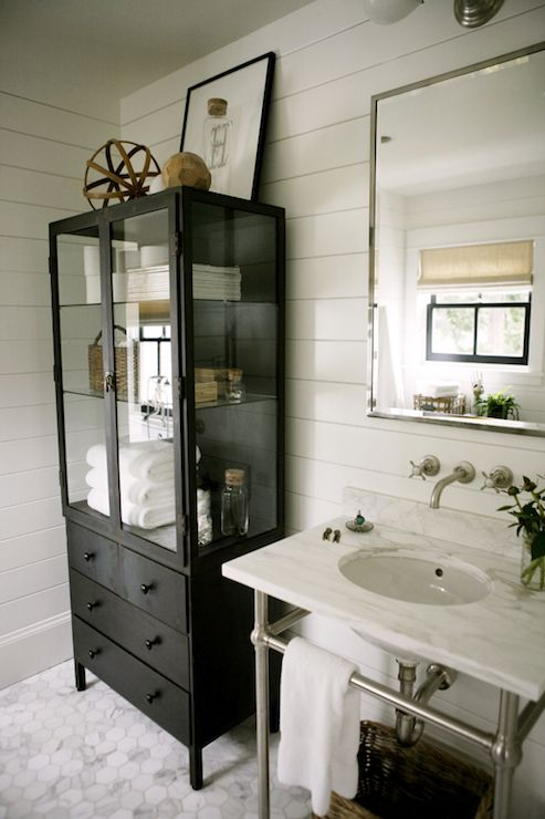 hic cottage bathroom features polished nickel mirror over white marble top washstand paired with wall mounted spigot faucet with hot and cold handles on tongue and groove backsplash situated next to black linen cabinet with glass doors atop white marble hex tiled floor.