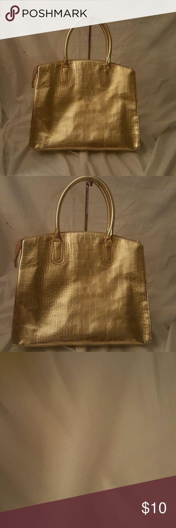 Gold tote handbag new.no tags Gorgeous and spacious gold tote bag, new no tags. Looks gorgeous with a cute top and white pants for a stunning spring look. Bags Totes