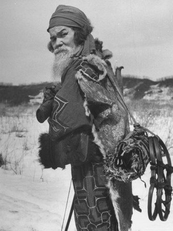 Ainu Village Chief with a dog skin protecting his back from the biting cold.