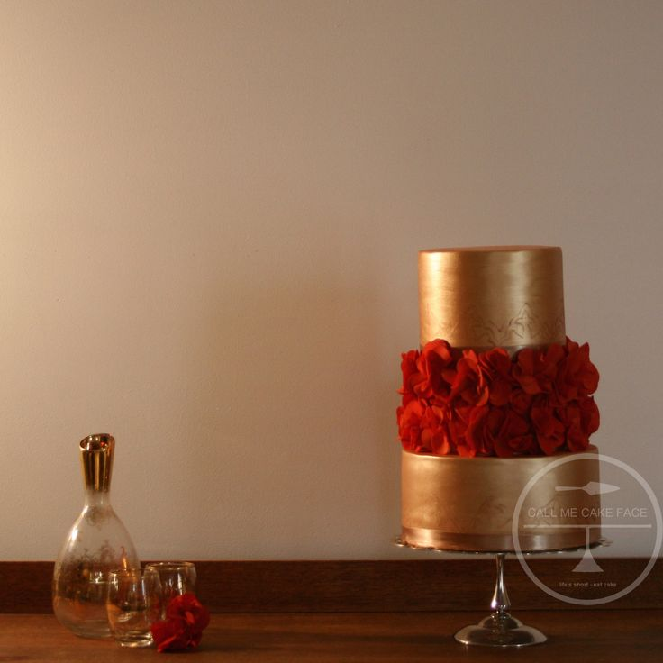 Petite three tier cake in old gold lustre and bright red Scrunch Roses.