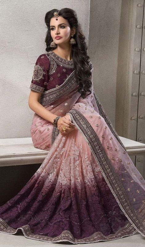 Captivate the essence of elegance in your daily looks wrapped in this purple and pink color shade embroidered net sari. The ethnic lace, resham and stones work on apparel adds a sign of elegance statement with your look. #ethnicdesignsaree #womenonlinesaris #latestfancysari