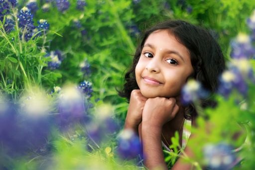 Little girl sitting in a field of flowers. Kids spring picture ideas.