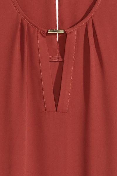 Camicetta senza maniche: Camicetta senza maniche in tessuto con gioiello in metallo sullo scollo. Apertura sulla schiena con bottone nascosto sulla nuca. Linea arrotondata in basso, leggermente più lunga dietro.