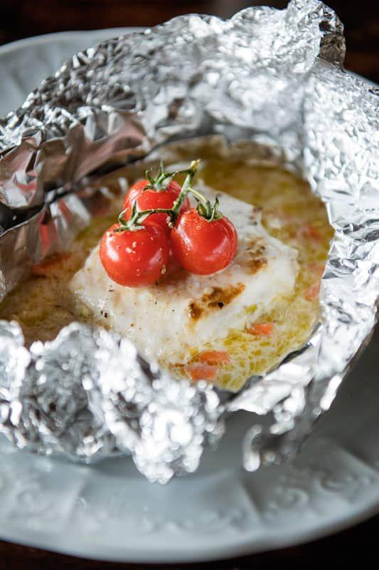 1. Schil de wortelen en reinig de prei. Snij de groenten in kleine, gelijke stukken. 2. Voorzie 3 kerstomaatjes aan een steeltje per papillot. 3. Scheur een groot stuk aluminiumfolie af en strijk in met olijfolie. 4. Verwarm de oven voor op 200°C. 5.