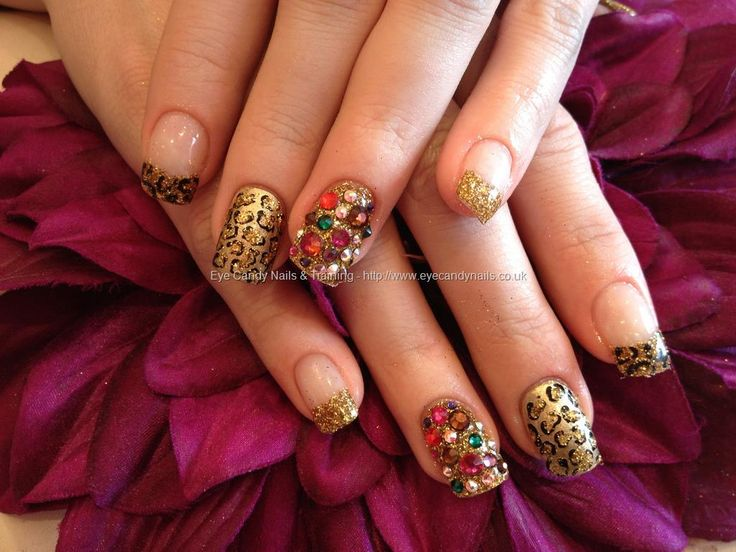 Acrylic nails with gold glitter dust and multi coloured Swarovski crystals on ring finger