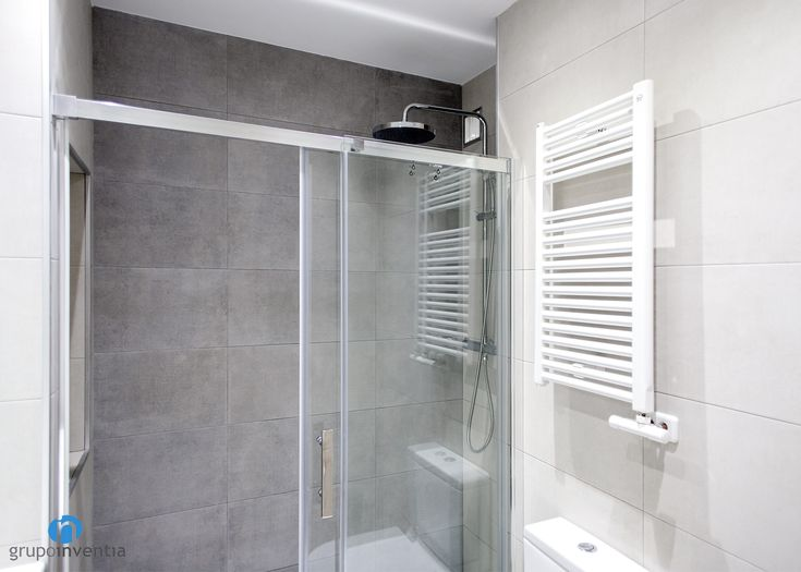 La ducha esta protegida con mamparas de puertas correderas ...