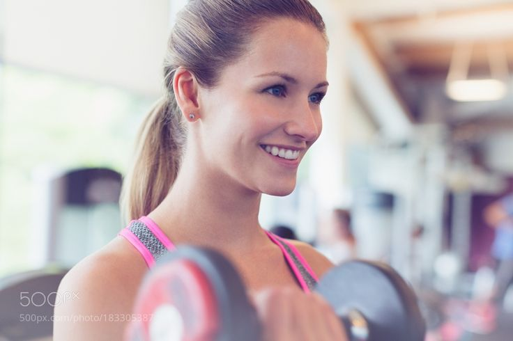 """Close up smiling woman doing dumbbell biceps curls at gym"" by caia_images via 500px.com Shop Fitness at FitnessCurious.com"