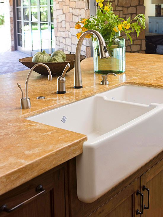 Middle Ground: Sink Area On the central island, a large farmhouse sink rests cozily amid granite countertops. The warm hues of the stone echo those featured in the nearby backsplash and in the home's rough-cut limestone walls. The plentiful counter space allows the island to function as a work zone and eating area all in one.