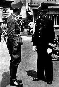 A Luftwaffe officer talks to a policeman in German-occupied St Helier, Jersey, UK