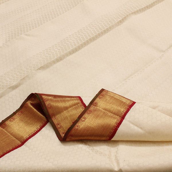The colour combination of cream and maroon is always in style. A classic. The cream body is patterned with small, tone-on-tone floral motifs while the medium wide maroon border features the leaf and paisley motifs. The pallu is an elaborate interwoven design flanked on one side by rows of paisley and floral motifs. The blouse is richly done in plain maroon containing a subtle design pattern. Code 100125526.