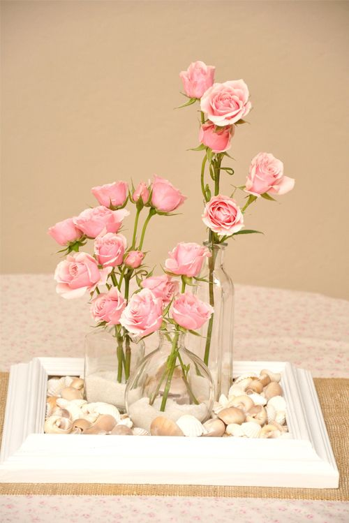 DIY frame centerpiece..frame, shells, clear bottles and flowers. Found on luna and chloe weddings #DIY #centerpiece