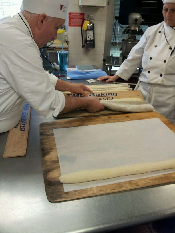 Transferring the shaped baguettes to the parchmeant paper for scoring and then into the 450 degree oven directly onto the hearth.