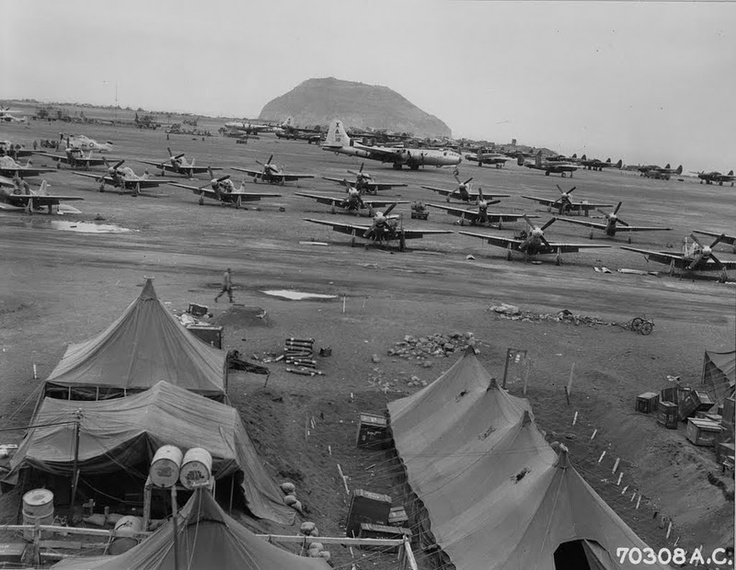 Iwo Jima Fighters and Bombers  8 April 1945, the day after the first fighter+bomber raid on Japan, Boeing B-29's, North American P-51's and Northrop P-61's are parked along Number #1 strip on Iwo Jima, Bonin Islands. Mt. Suribachi may be seen in the background. 78th Fighter Squadron