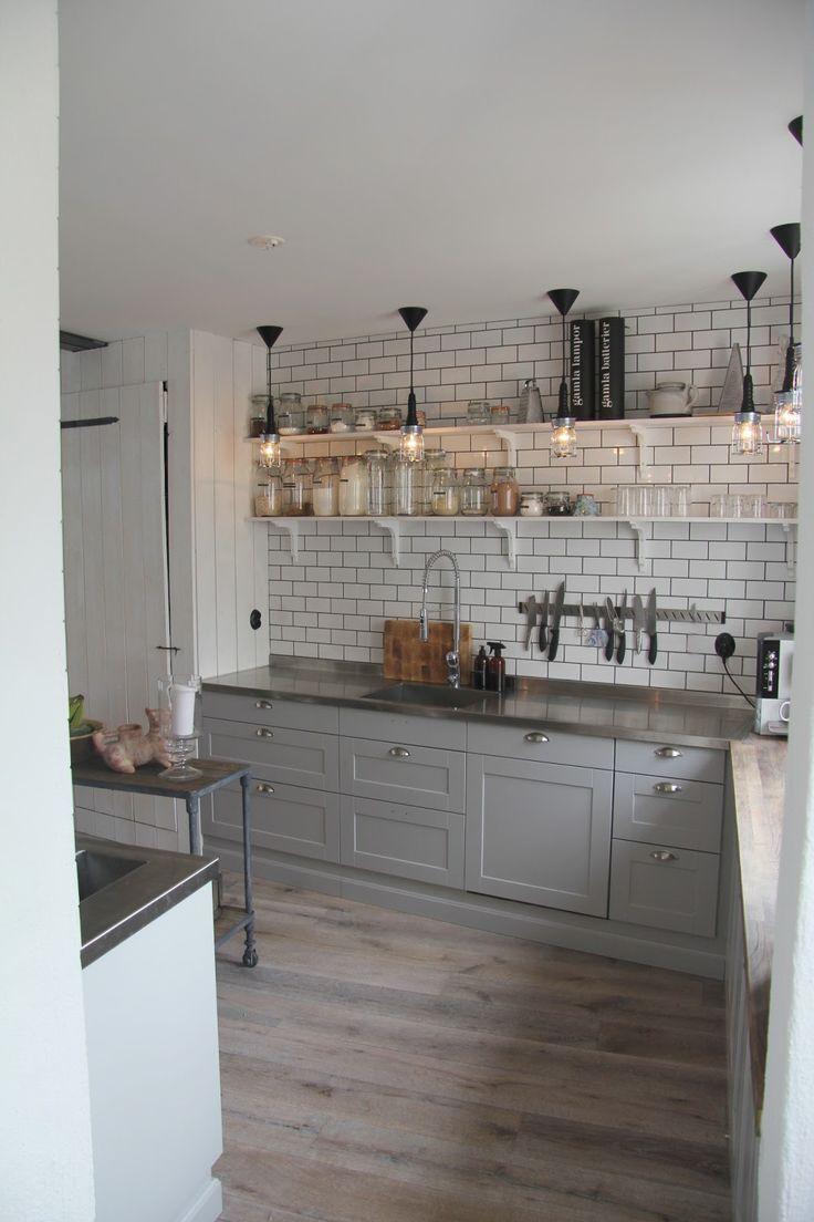 Gray cabinets. Steel countertops. White tiles. Design by Carola Sahlen.