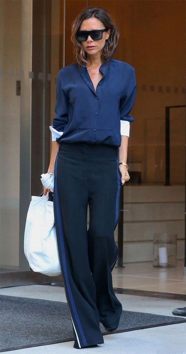 Victoria Beckham usa calça pantalona sporty azul marinho e camisa em mesmo tom.