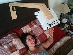 Wood, stretch shoelaces, corrugated plastic cardboard -- viola! A homemade iPad bed stand