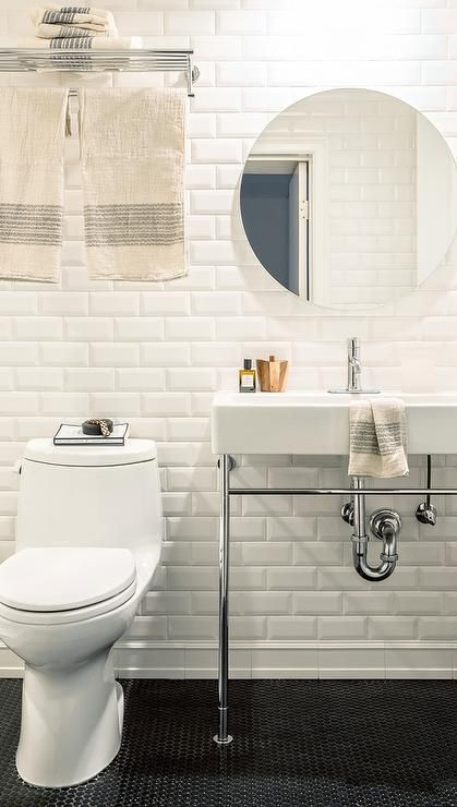 White bathroom features walls covered in white beveled subway tiles lined with a 2 leg washstand, atop a black penny tiled floor accented with black grout, under a round frameless mirror.