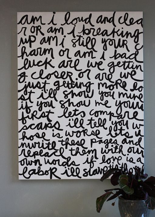 """large white canvas with hand-painted cursive """"rise against"""" lyrics makes a statement"""