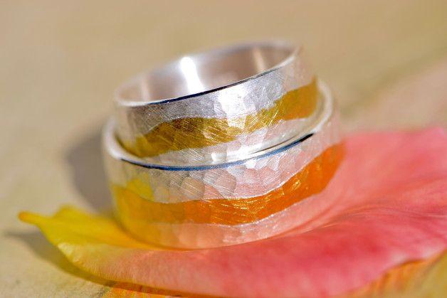 Schön und solide Eheringe aus Silber mit eingearbeitetem 900-er Goldstreifen und gehämmerter Oberfläche.  Da sie innen leicht abgerundet(bombiert) sind, sind sie trotz der Breite sehr angenehm zu...