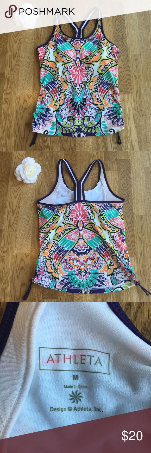 "Athleta ""Ready to Run"" Tankini Top Beautiful patterned Athleta tankini top! Advertised as being great for triathlons and other races/events that involve both running and swimming. Made of swimsuit material and has a built in support bra for the running portion of the event! Sides can be tightened to keep it in place! There is a pink mark/discoloration on the inside where the tag/logo is (see pic) but it does not affect the outside! Ask any questions and feel free to make an offer :) Athleta…"